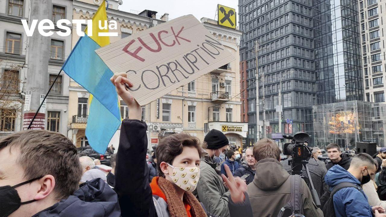 Протестующие держат плакаты и флаги