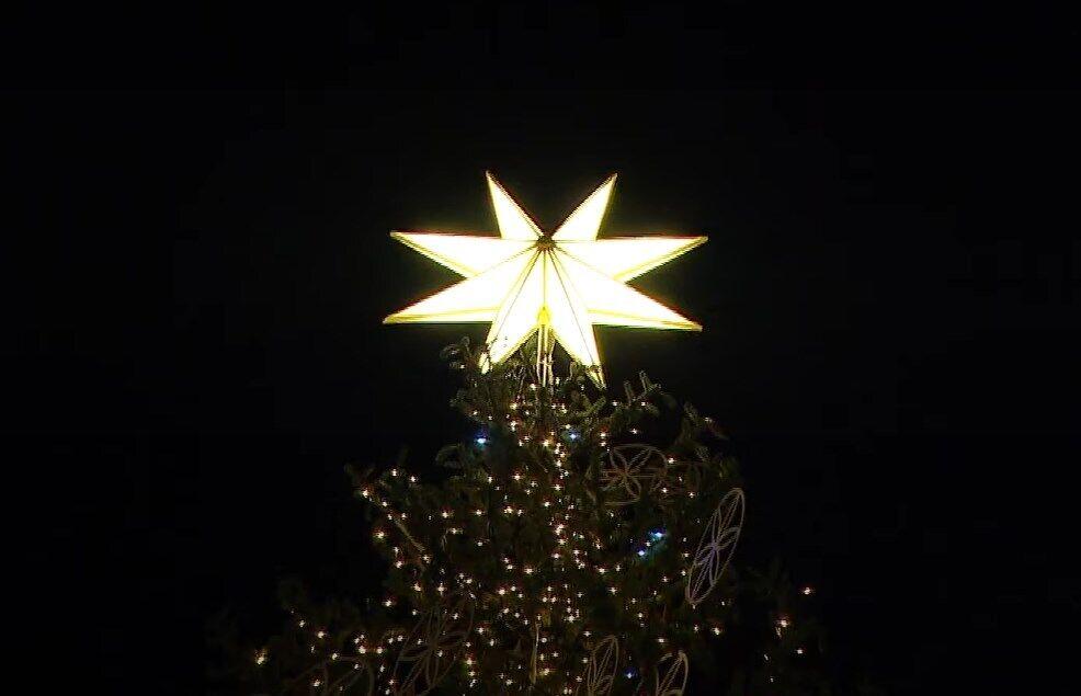 Елка украшена рождественской звездой.