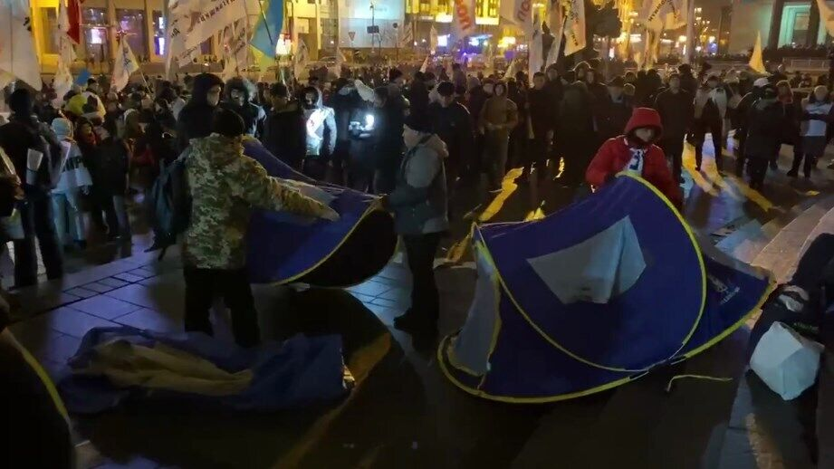 Протестующие убирают палатки.