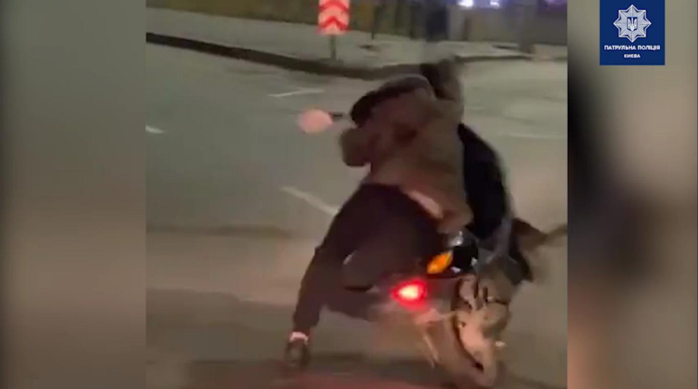 Мужчина пытается удержать мопед