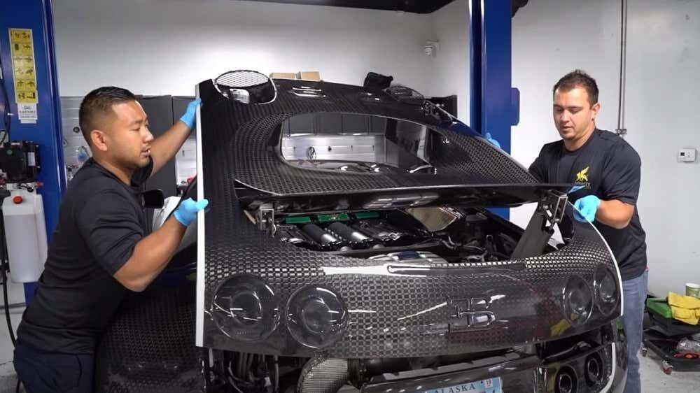 Замена моторного масла Bugatti Veyron начинается с демонтажа части кузова.