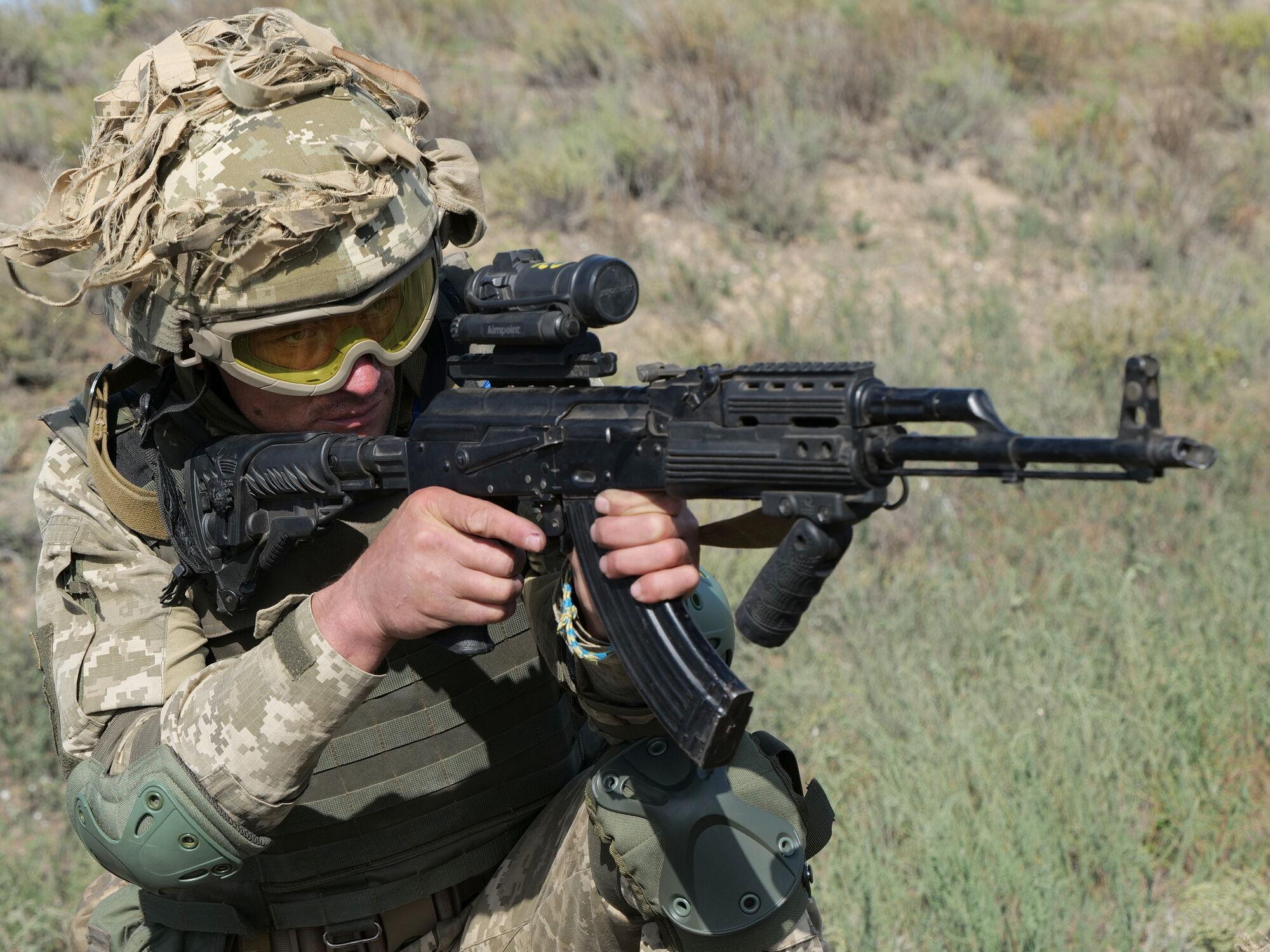 Воин ВСУ стреляет из автомата во время учений.