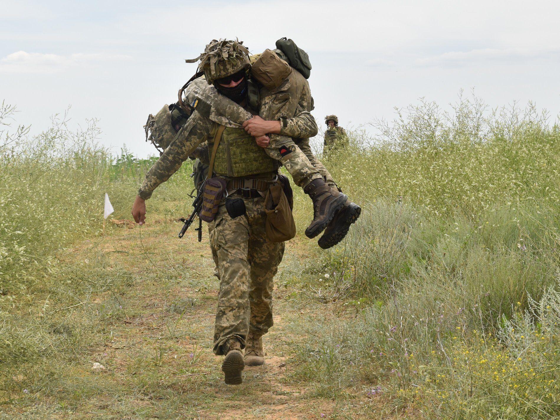 Защитники отрабатывают эвакуацию раненых с поля боя.