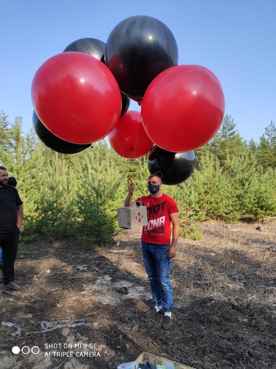 Открытки привязали к большим воздушным шарикам красного и черного цвета