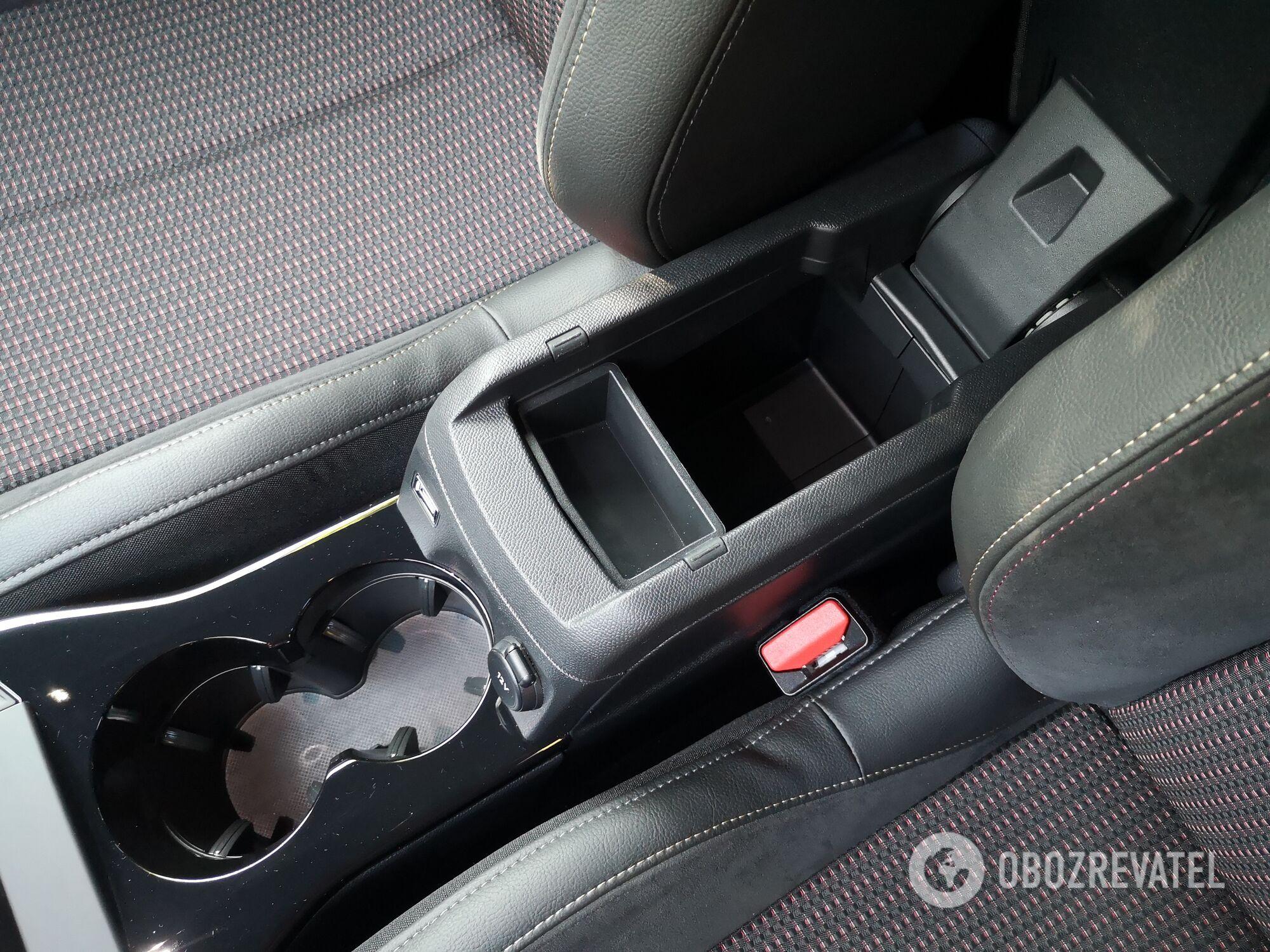 Между передними сиденьями есть два подстаканника и глубокое отделение для мелочей в подлокотнике. Фото:
