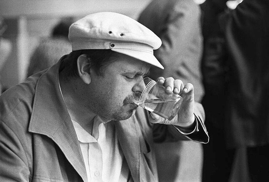 """Чоловік у кепці прямо на вулиці заправляється """"пальним"""" із добре відомого радянського стаканчика з тонкого скла з п'ятьма смужками тонкої емалі."""