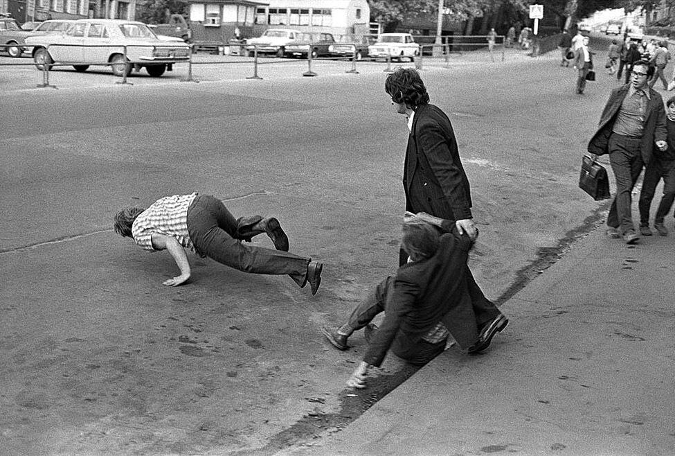 Фотограф відобразив п'яного чоловіка за долю секунди до падіння обличчям об асфальт. На передньому плані падає ще один, а тверезіший товариш намагається його утримати.