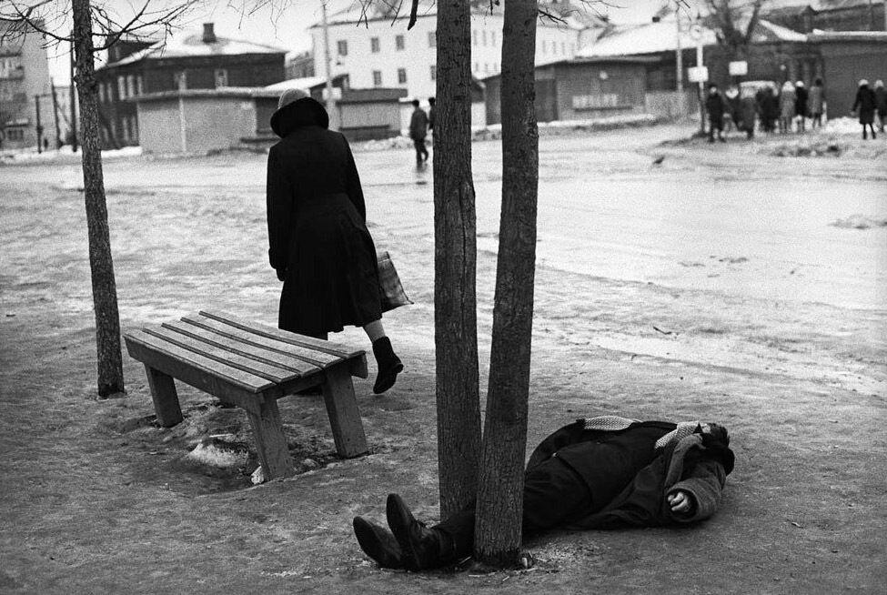 Повз лежачого на льоду і повільно замерзаючого п'яниці байдуже проходить жінка в чорному пальто, а на дальньому плані також байдуже йдуть у своїх справах безліч інших людей.