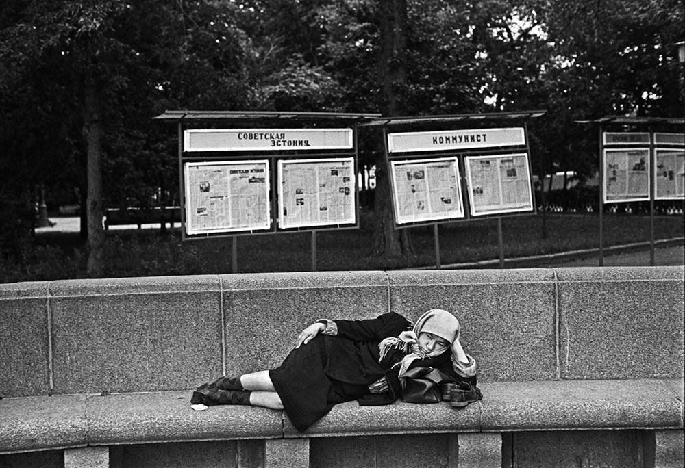 """Бідно одягнена жінка лежить на гранітній приступці, а на задньому плані видно щити з періодичними виданнями – """"Радянська Естонія"""", """"Комуніст"""" та ін., у яких радянським громадянам розповідали про те, як добре вони живуть."""