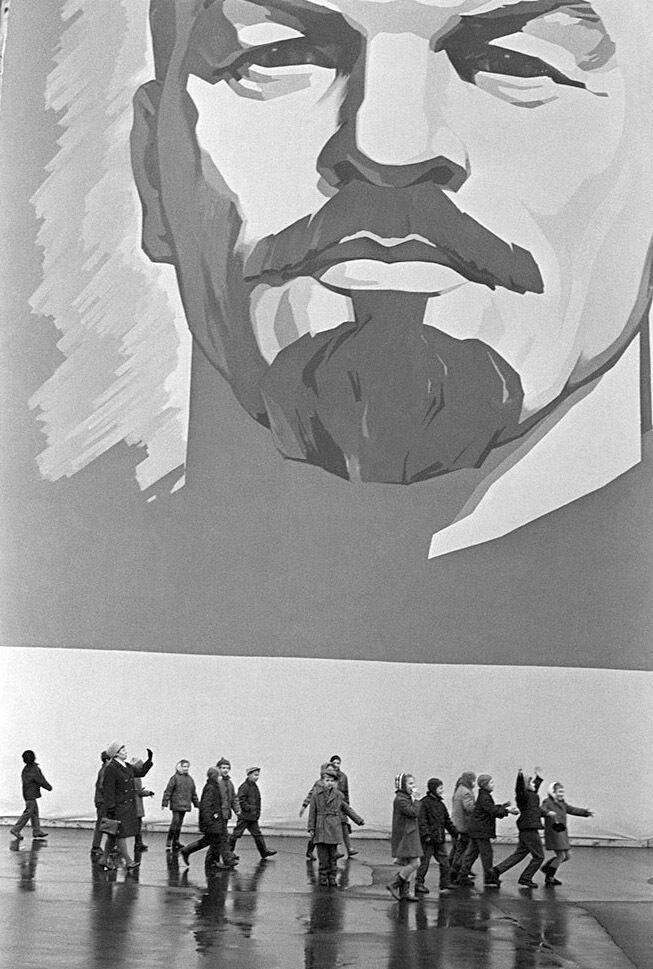 """Діти йдуть до школи на фоні зображення неймовірно величезної голови """"вічно живого"""" Леніна."""