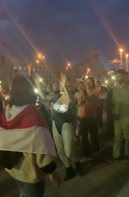 Жінку знімала дівчина з прапором-символом опозиції.