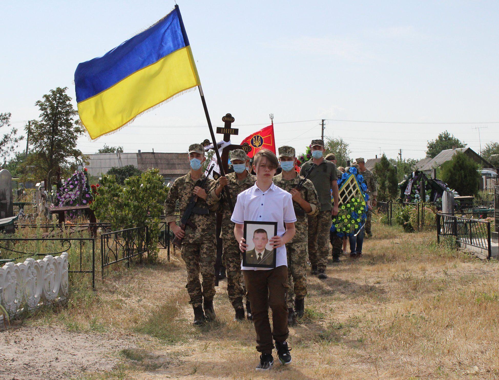 Сын погибшего воина ВСУ нес его портрет.