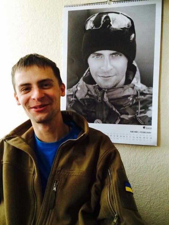 """Мирослав Баженов на фоне собственного фото в календаре """"Вернись живым""""."""