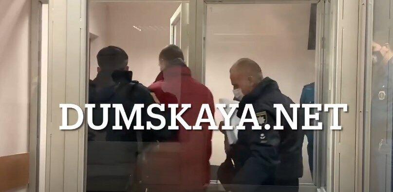 Поліція веде підозрюваного з суду.