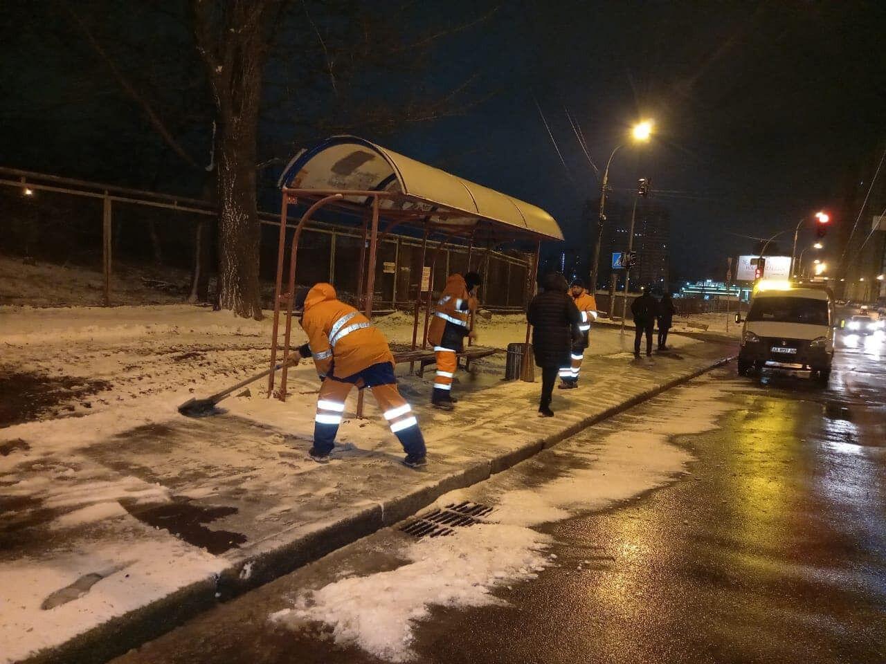 Коммунальщики чистят остановки от снега.