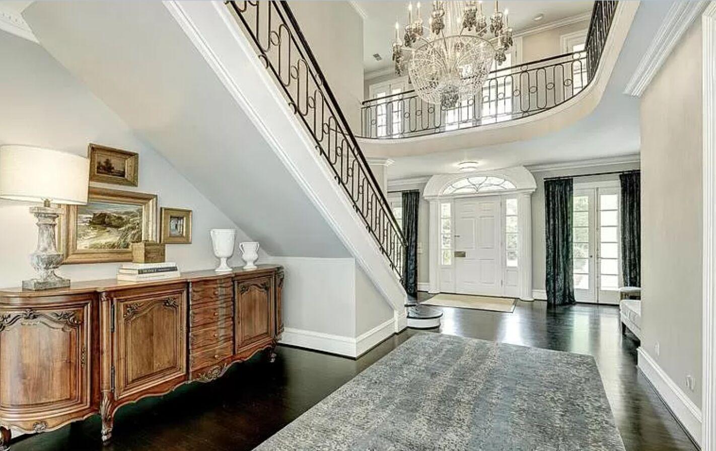 Усередині резиденції – мармурові сходи, високі стелі та інтер'єри в стриманих світлих тонах.