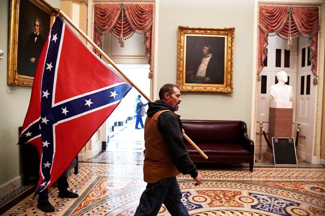Сторонник Трампа несет боевой флаг Конфедерации на втором этаже Капитолия