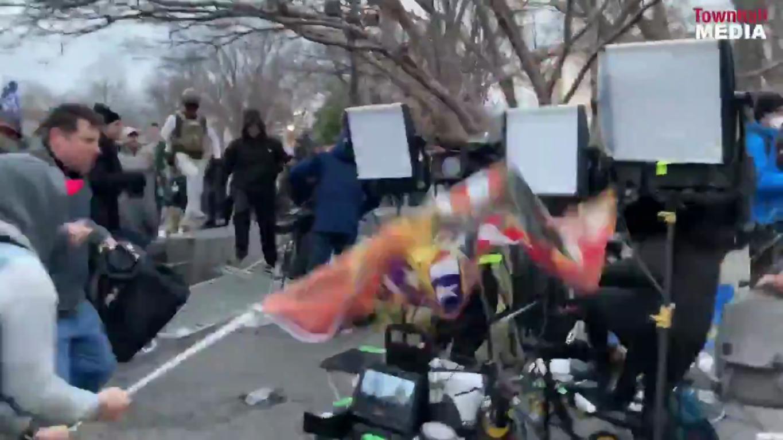 Мужчина бьет флагом технику журналистов