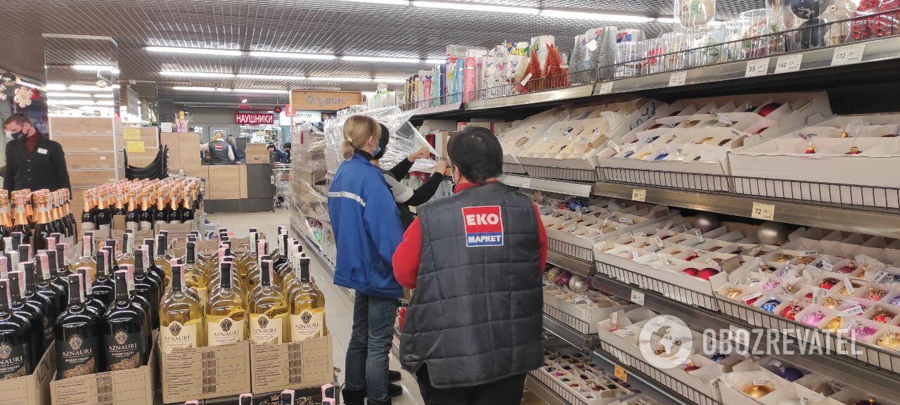 Співробітники супермаркету обмотують товари в плівку