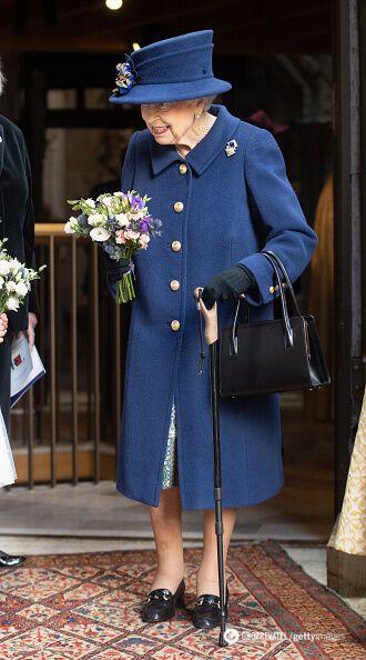 Королева Великобританії з ціпком на публічному заході.
