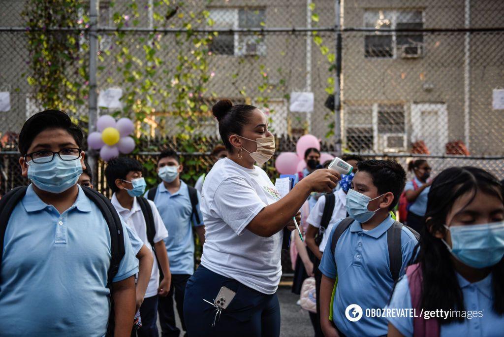 На фото нью-йоркська вчителька міряє температуру учням