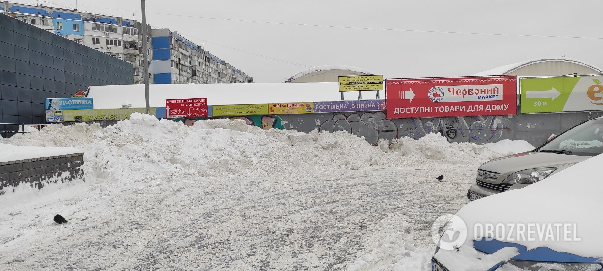 На Троещине снег со стоянки у магазина сбросили возле рынка.