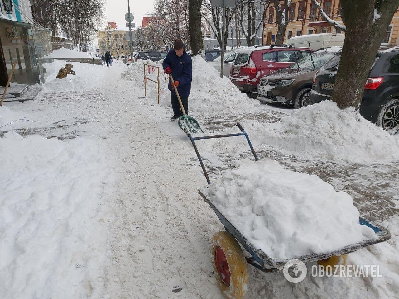 На улицах коммунальщики вручную убирают снег.