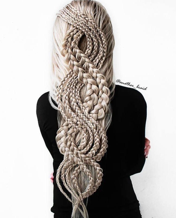 Девушка украшает натуральные волосы оригинальным плетением.
