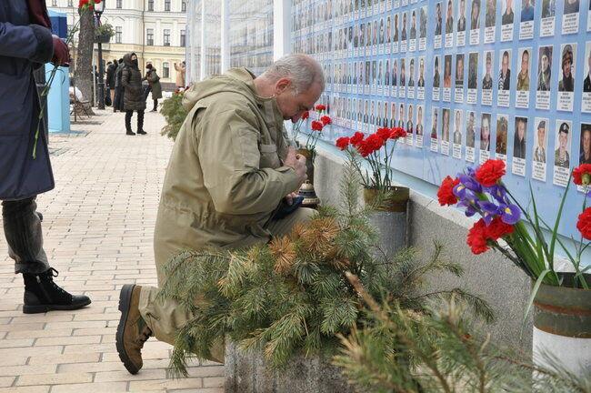 Мужчина молится у Стены памяти павших за Украину
