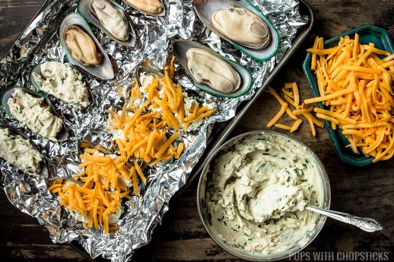 Мидии нужно смазать чесночным маслом и посыпать сыром.