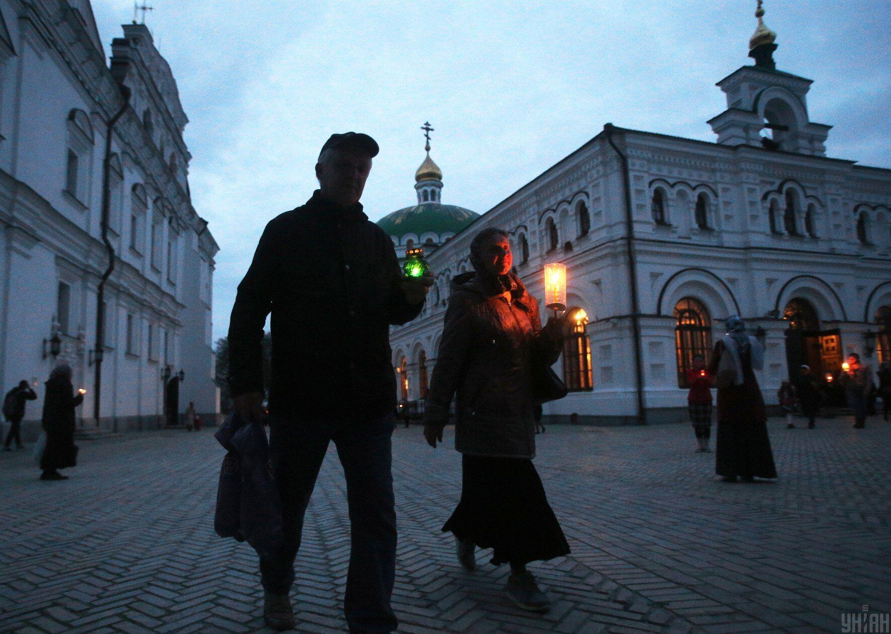 Зажженные свечи после службы в Чистый четверг верующие несут домой
