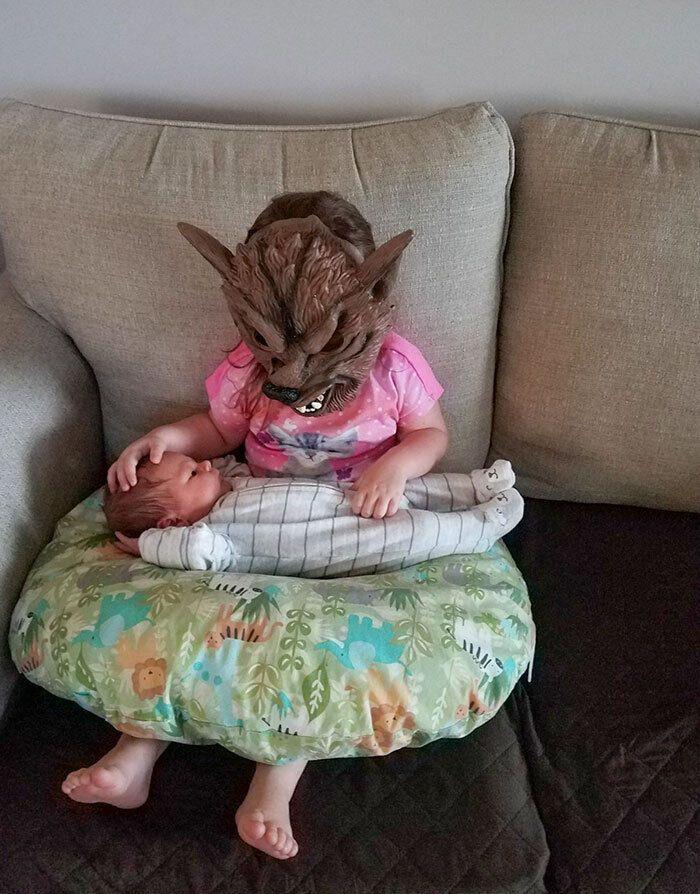 Девочка укачивает младшего брата.