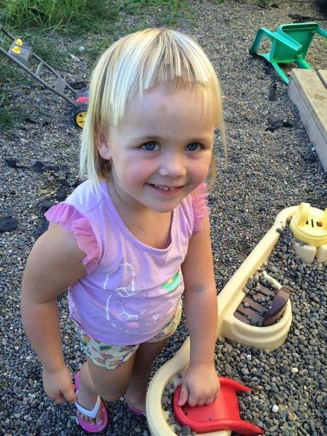 Девочка подправила ножницами прическу.