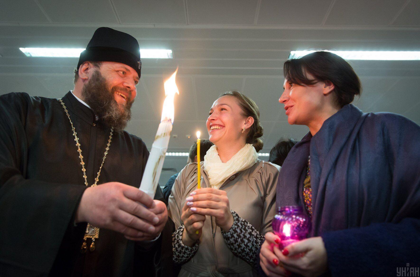 """Люди зустрічають Благодатний вогонь з Єрусалиму в аеропорту """"Бориспіль"""""""