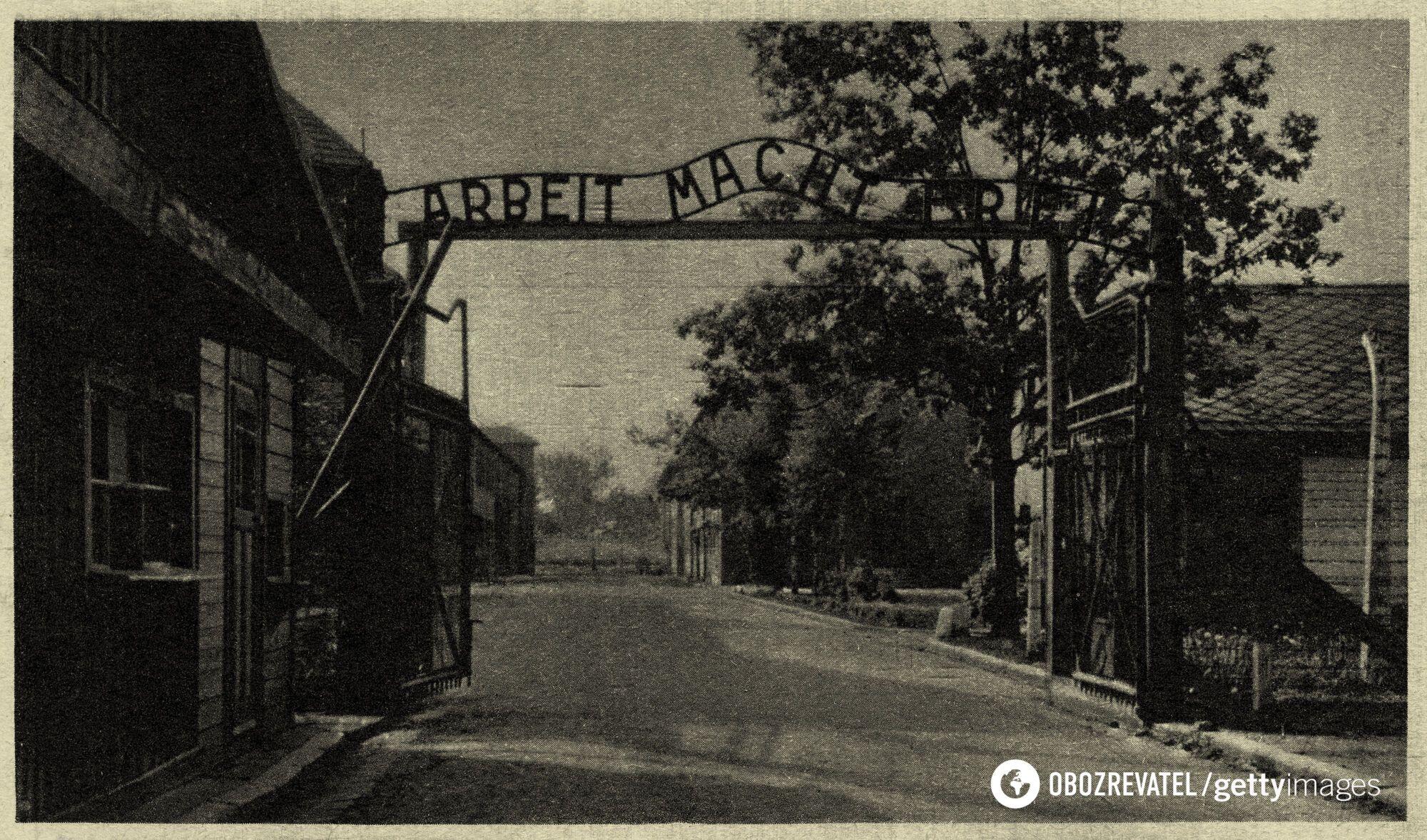 """Открытка концлагеря Освенцим I, вид на металлическую таблицу с надписью """"Arbeit Mach Frei"""" – """"Работа делает вас свободными"""""""
