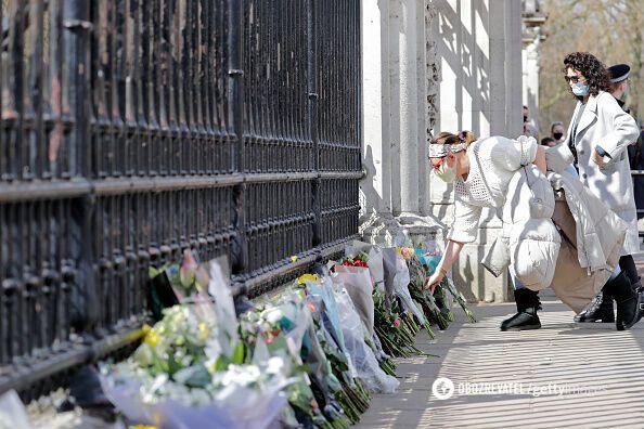 К Букингемскому дворцу несут цветы.