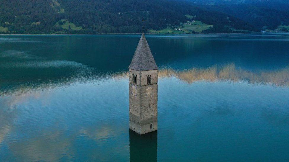 Шпиль, который возвышается над озером.