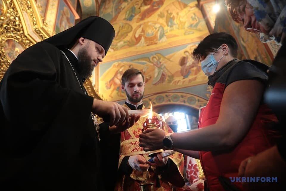 Священик запалює свічки