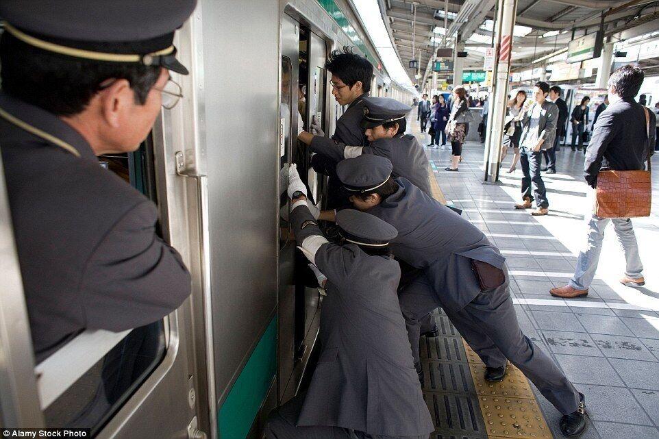 """В Японии есть люди, которые """"трамбуют"""" пассажиров в метро."""