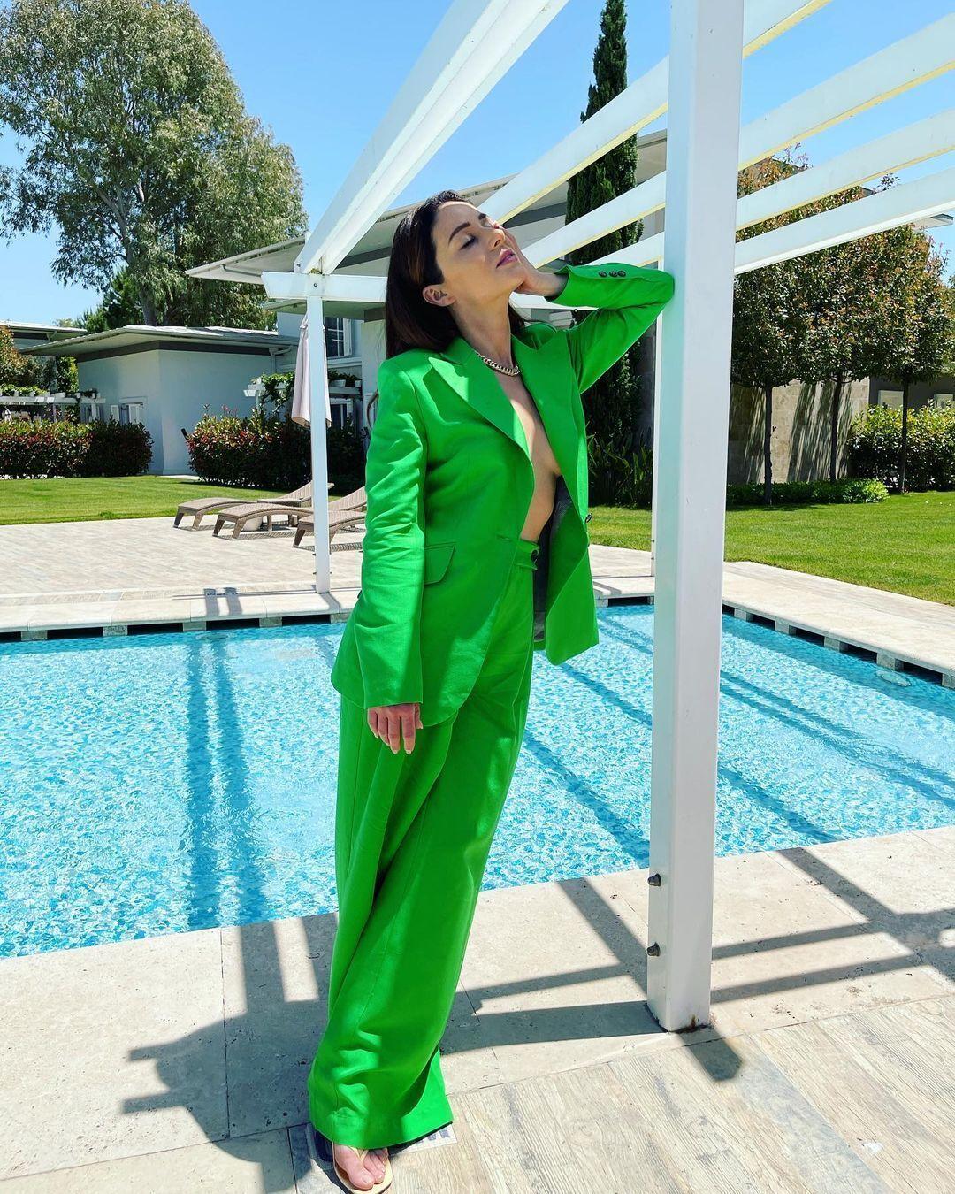 Злата Огневич позує в зеленому костюмі біля басейну