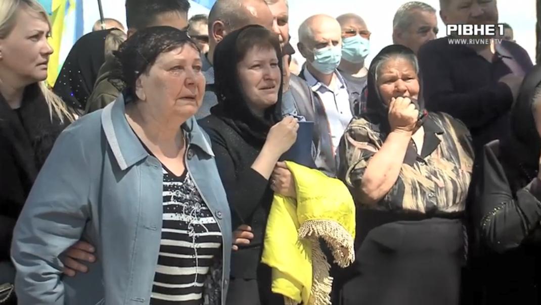 Мама Василя Килюшика тримає прапор, яким була покрита його труна