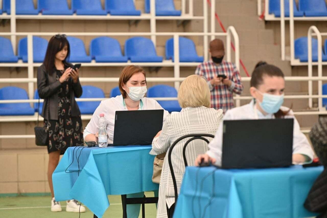 Люди працюють за столами прямо на стадіоні