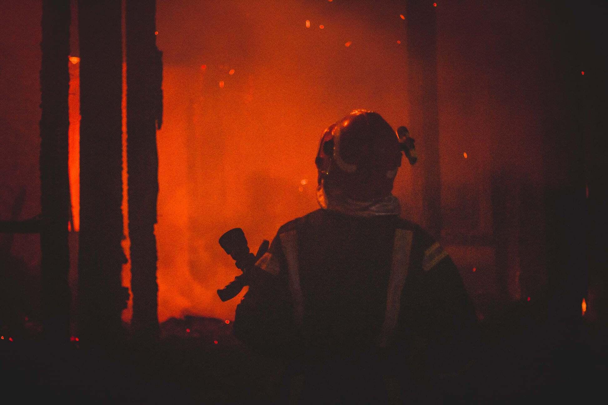 Пожежник бореться з відкритим вогнем на пожежі в Києві