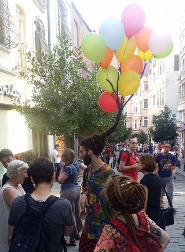 Эпатажная мужская прическа украшена воздушными шариками.