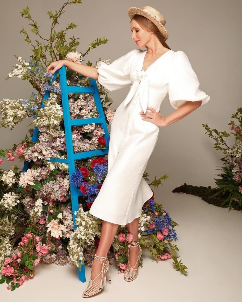 Осадчая позировала в белом платье.