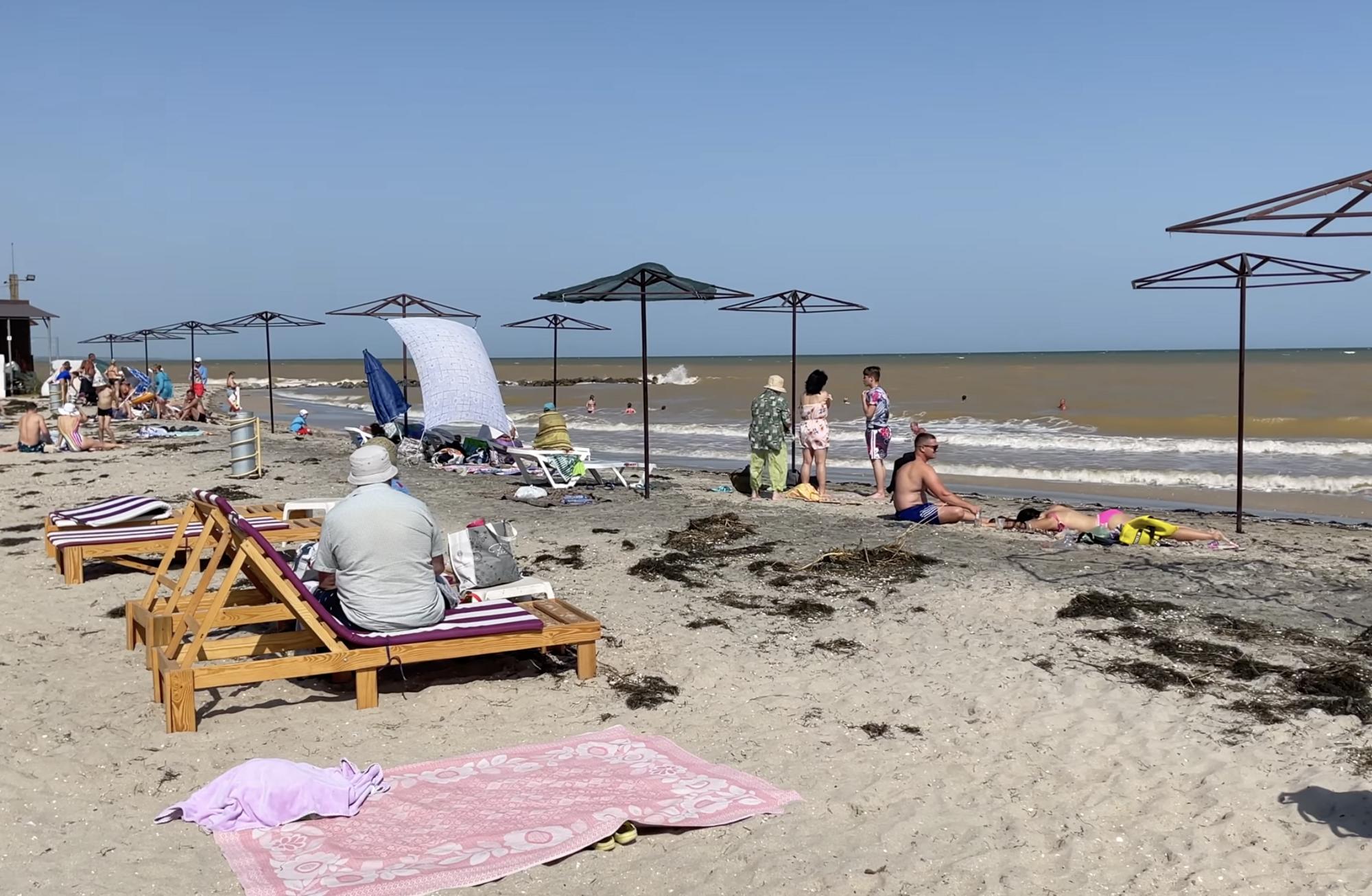 Туристы отдыхают на грязном пляже.