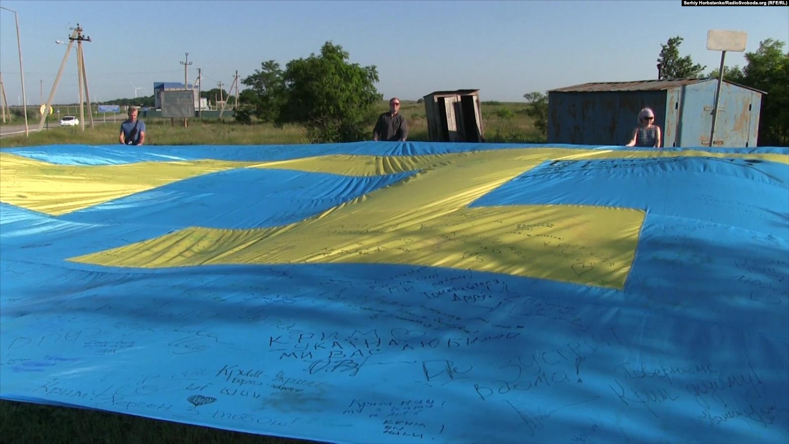 Первым флаг подписал национальный лидер крымских татар Мустафа Джемилев