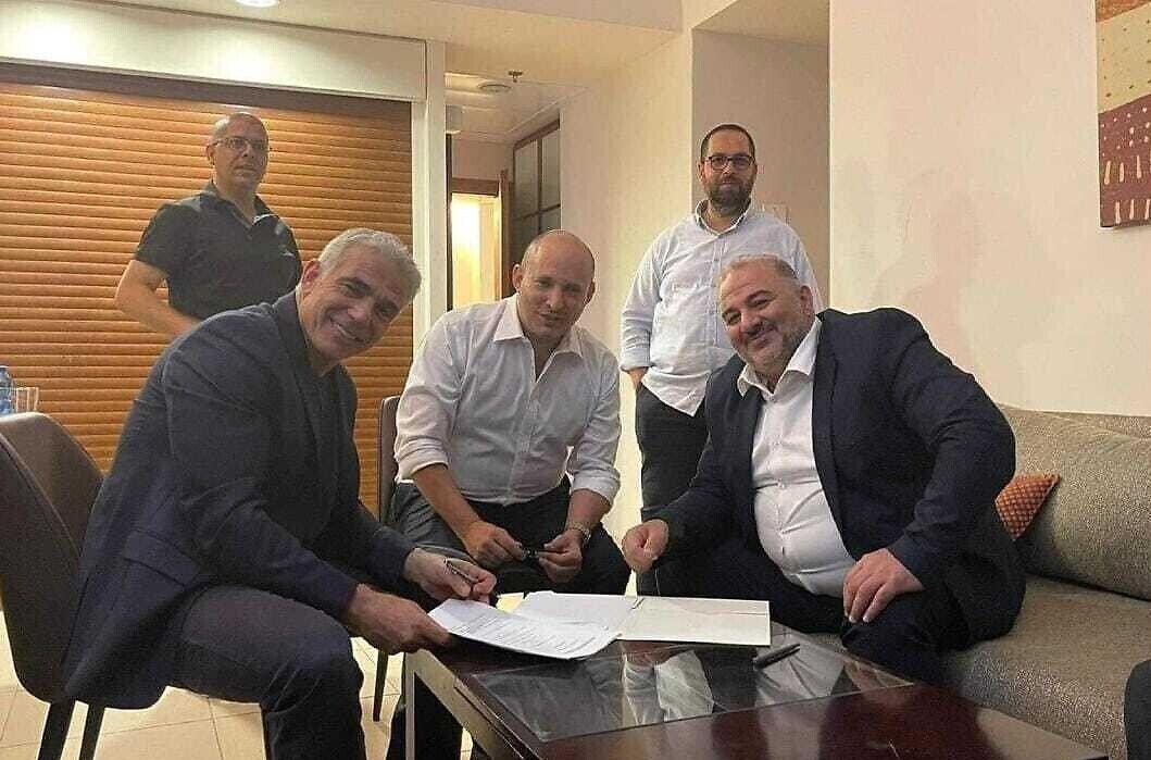 Яир Лапид (слева), Нафтали Беннетт (в центре) и Мансур Аббас подписывают коалиционное соглашение 2 июня 2021 года