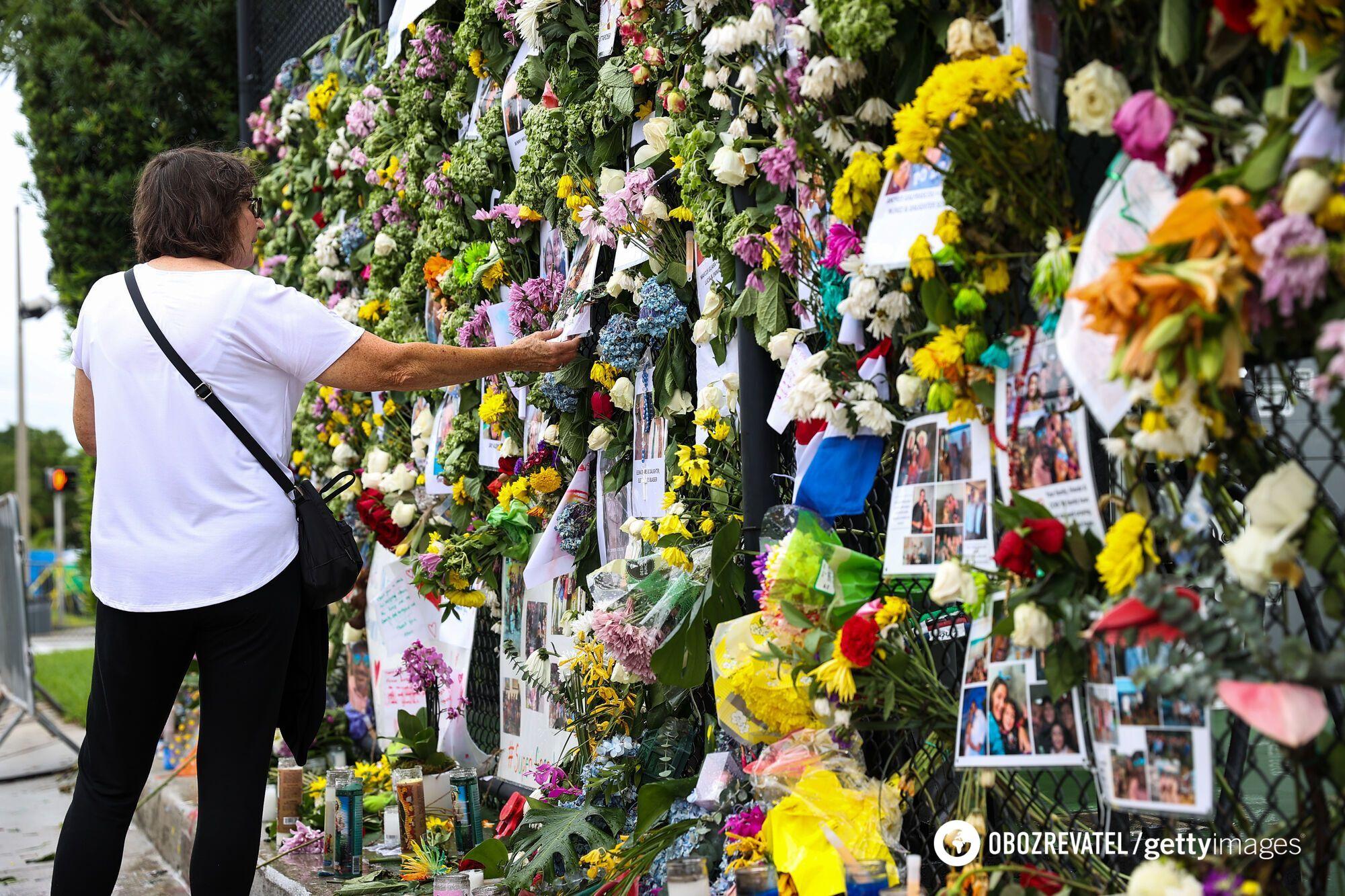 Люди приносят цветы к месту обрушения дома