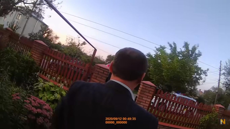 Прокурор вже майже зайшов в будинок, але копи завадили йому і повернули до автомобіля. На зображенні видно, як поліцейський йде за порушником до машини